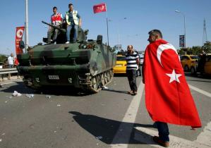 A man wrapped in a Turkish flag walks past a military vehicle in front of Sabiha Airport, in Istanbul