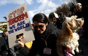 A tour guide holding her pet and a placard visits the site of Tuesday's suicide bomb attack at Sultanahmet square in Istanbul, Turkey January 14, 2016. REUTERS/Murad Sezer