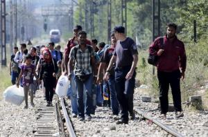 A Greek police officer guides migrants arriving to enter Macedonia