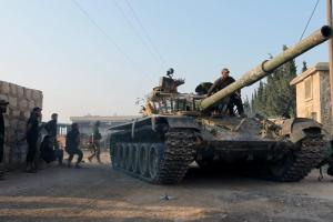 Rebel fighters ride a tank in an artillery academy of Aleppo
