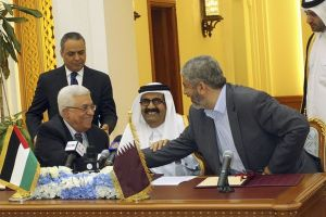 Palestinian President Abbas and Hamas leader Meshaal shake hands as Qatar's Emir Sheikh Hamad sits between them during an agreement signing ceremony in Doha