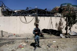 An Afghan policeman stands at the site of a car bomb attack in Kabul