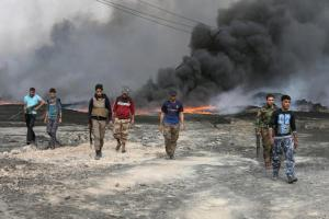 Tribal fighters walk as fire and smoke rises from oil wells, set ablaze by ISIS militants before ISIS militants fled the oil-producing region of Qayyara
