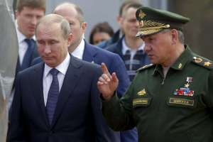 Russian President Putin listens to Defence Minister Shoigu as they arrive for opening of Army-2015 international military forum in Kubinka
