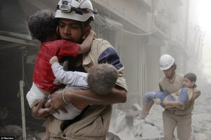 Syrian civil defense volunteers could be seen carrying children from the debris after air strikes in the rebel-held Aleppo town (Reuters)