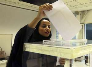 A Saudi woman casts her ballot at a polling center during municipal elections in Riyadh, Saudi Arabia, Saturday, Dec. 12.