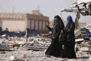 Women walk in the war-ravaged town of al-Shadadi in Hasaka province, northeast Syria, on Friday.