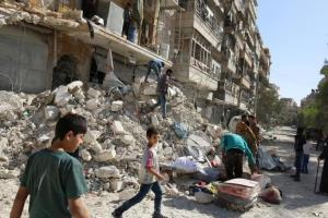 People remove belongings from a damaged site after an air strike Sunday in the rebel-held besieged al-Qaterji neighbourhood of Aleppo