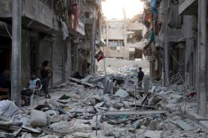 Residents inspect a damaged site after an airstrike in the besieged rebel-held al-Qaterji neighbourhood of Aleppo