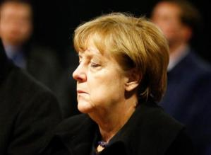 German Chancellor Angela Merkel reacts before she signs the condolence book at the Gedaechniskirche in Berlin