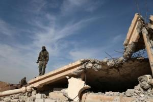 An Syrian Democratic Forces fighter stands with his weapon on the rubble of a destroyed building, north of Raqqa city