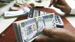 A Saudi money changer counting Saudi Riyals in Riyadh, Saudi Arabia.