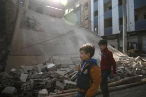 Boys walk near a damaged building in the rebel held besieged city of Douma, in the eastern Damascus suburb of Ghouta