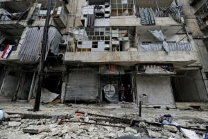 Boys stand amid the damage in the government-held al-Shaar neighborhood of Aleppo, during a media tour, Syria December 13, 2016. REUTERS/Omar Sanadiki