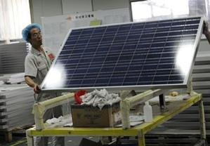 A worker lifts a solar panel in the Yingli Solar factory