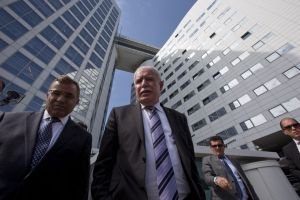 Palestinian Authority Foreign Minister Riyad Malki, center, waits on the steps of the International Criminal Court after answering questions of reporters in The Hague, Netherlands, Thursday, June 25, 2015.
