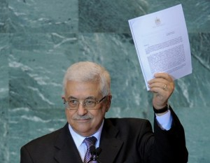 Mahmoud Abbas holds a copy of the letter requesting Palestinian statehood as he speaks during the United Nations General Assembly on 23 September, 2011 (AFP)