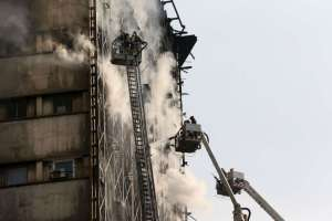 Iranian firefighters work to extinguish fire of the Plasco building in central Tehran, Iran, Thursday, Jan. 19, 2017. A high-rise building in Tehran engulfed by a fire collapsed on Thursday as scores of firefighters battled the blaze. (AP Photo/Vahid Salemi)