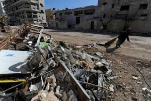 A woman walks past debris along a street in Aleppo's Belleramoun Industrial Zone