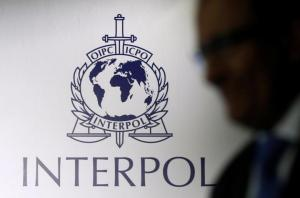 A man passes an Interpol logo during the handing over ceremony of the new premises for Interpol's Global Complex for Innovation, a research and development facility, in Singapore September 30, 2014. REUTERS/Edgar Su/File Photo