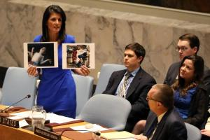 U.S. Ambassador to the United Nations Nikki Haley holds photographs of victims during a meeting at the United Nations Security Council on Syria at the United Nations Headquarters in New York City