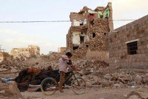A boy rides a bike through the rubble Yemen in March 2015