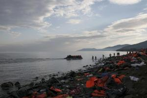 Refugees and migrants on an inflatable raft approach the shores of the Greek island of Lesbos