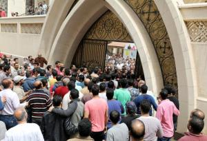 Egyptians gather in front of a Coptic church that was bombed on Sunday in Tanta