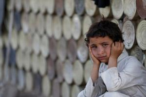 Boy looks on as he sits next to a hut at a camp for people displaced by the war near Sanaa, Yemen