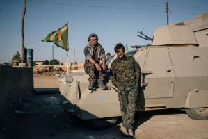 Lucas Chapman, left, and Brace Belden, U.S. volunteers with the People's Protection Units, or YPG, pose for a portrait next to a homemade armored vehicle in a rear base near Tal Samin, Syria.