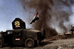 An explosion hits near a vehicle belonging to Iraq's elite Rapid Response Division on February 25, 2017, during the assault to retake the western half of Mosul, which is still occupied by ISIS group jihadists