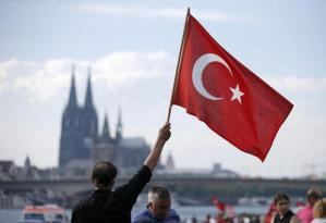A supporter of Turkish President Erdogan waves a Turkish flag during a pro-government protest in Cologne