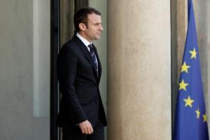 French President Emmanuel Macron waits for a guest on the steps at the Elysee Palace in Paris