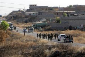 Kurdish Peshmerga forces gather in a village east of Mosul, Iraq