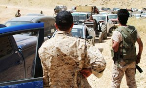 Armed men stand guard as a convoy of Syrian refugees leaves Arsal towards Qalamoun on July 12, 2017.