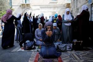 Palestinian women pray as others shout slogans outside the compound known to Muslims as Noble Sanctuary and to Jews as Temple Mount, in Jerusalem's Old City