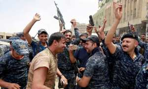 Iraqi police celebrate in the old city of Mosul.