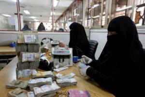 Workers count Yemeni currency at the Central Bank of Yemen in Sanaa