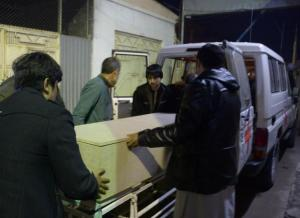 Afghan men unload a coffin of killed ICRC employee from a car at a hospital in Mazar-i-Sharif