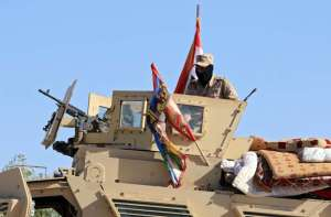 Iraqi soldiers ride in military vehicles in Zumar