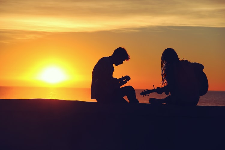 Boy and Girl Playing Guitar during a sunset