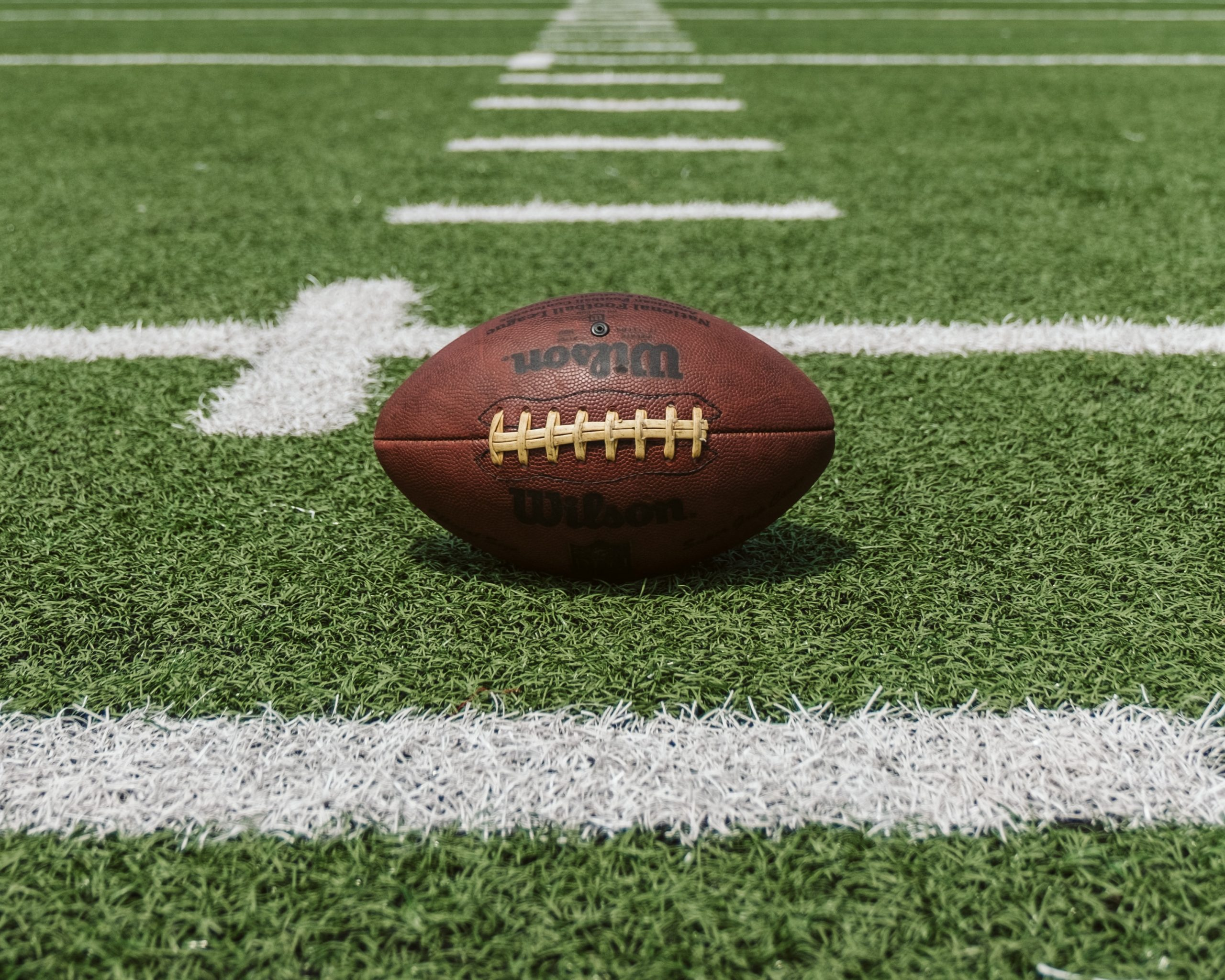 A picture of a football laying on a football field.
