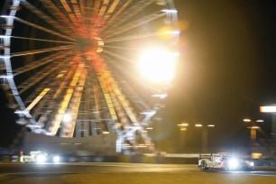 #20 Porsche races past the ferris wheel