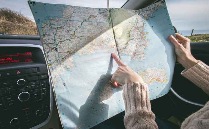 person wearing beige sweater holding map inside vehicle