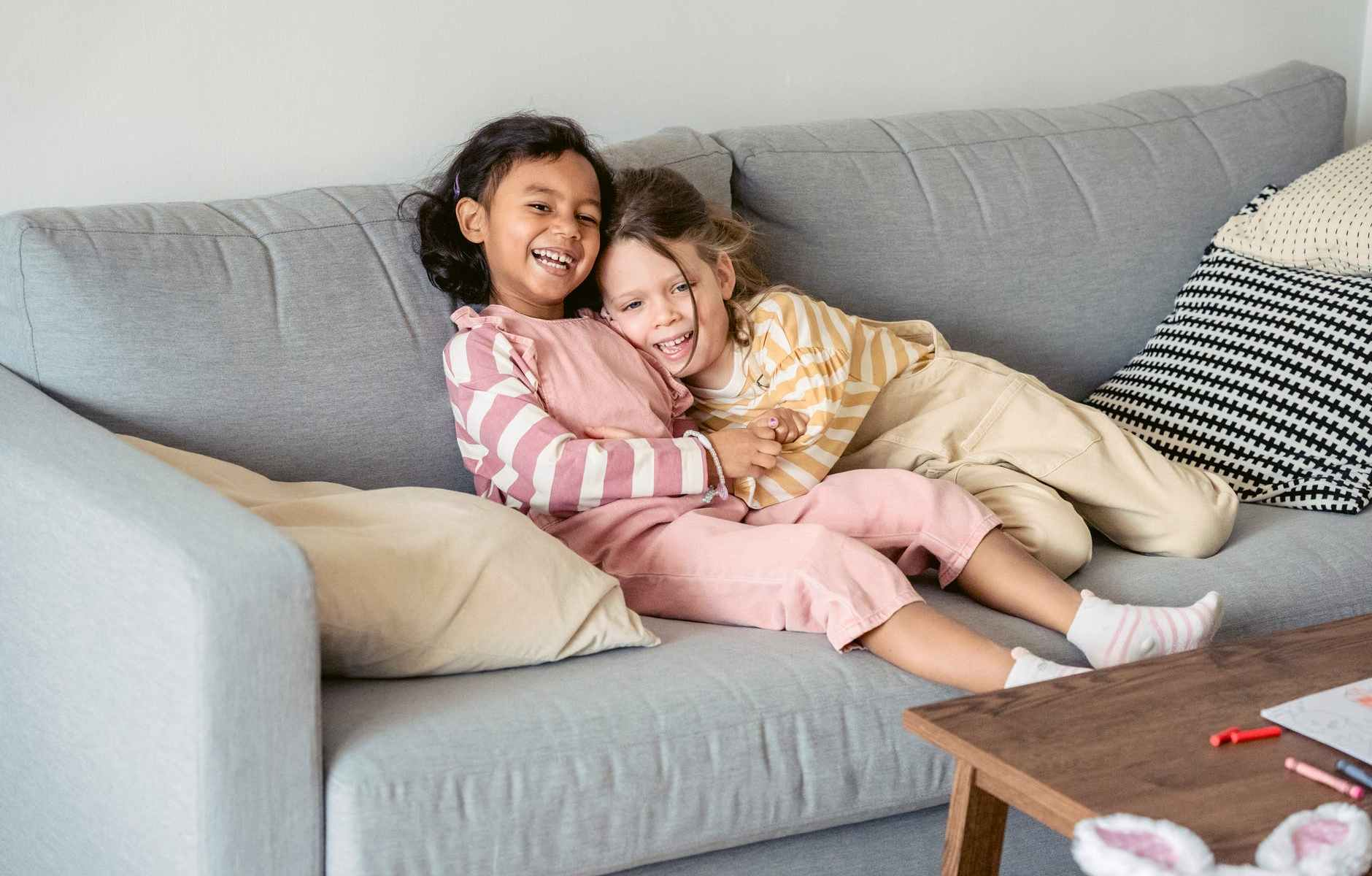 laughing diverse girls embracing gently on sofa
