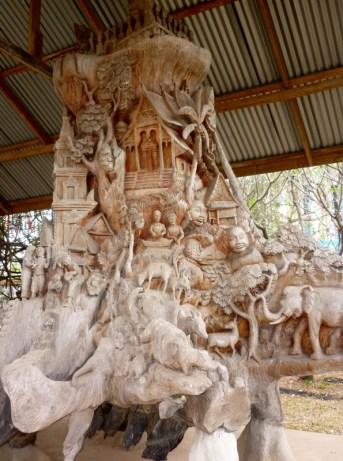 Etwa drei Meter hohe Wurzel vor dem Nationalmuseum in Vientiane: die preisgekrönte Arbeit zeigt Szenen aus laotischer Geschichte und Tradition. Die Arbeit ist unglaublich interessant anzusehen, man findet in jedem Eck der Wurzel neue Motive und Figuren!