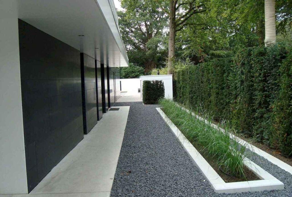 Jardim com brita em parte da pavimentação.