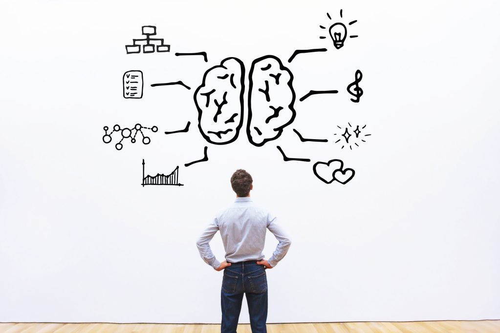 Homem olhando para parede com imagem de cérebro conectado a imagens de habilidades