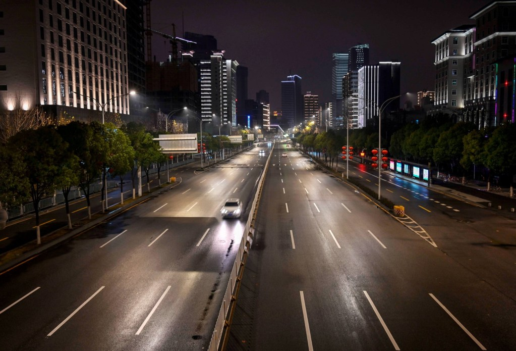 Avenida de Wuhan, na China, durante a noite, com baixo volume de tráfego.