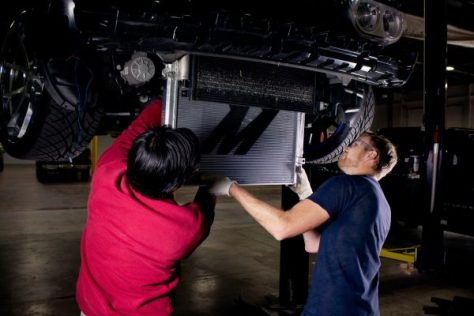 Jason and our newest project manager, Andrew, install the Mishimoto aluminum radiator into the Challenger.